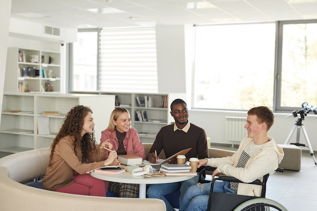 Seitenansicht bei einer multiethnischen gruppe von studenten, die in der universitätsbibliothek studieren, die jungen mann mit rollstuhl im vordergrund kennzeichnet,