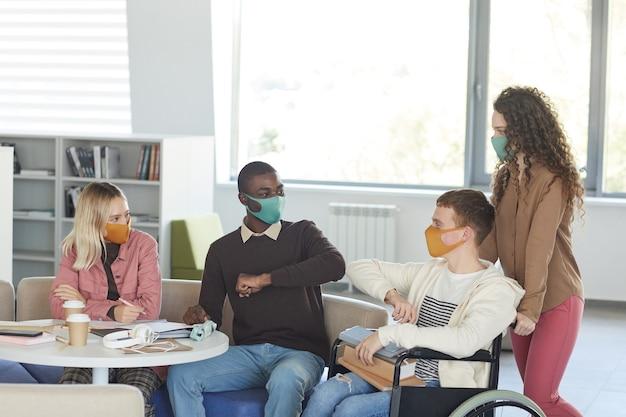Seitenansicht bei einer multiethnischen gruppe von studenten, die masken tragen, während sie in der universitätsbibliothek mit dem jungen mann studieren, der rollstuhl im vordergrund benutzt,