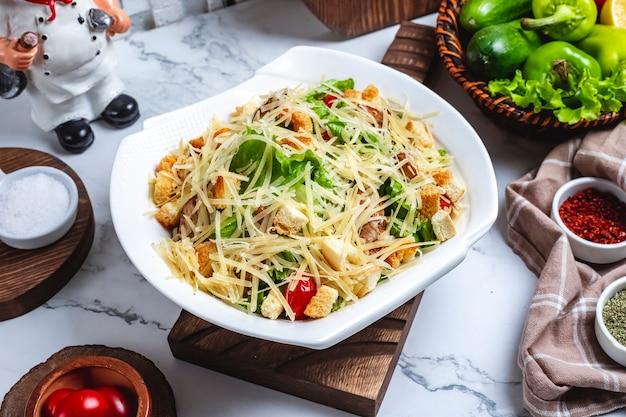 Seitenansicht caesar salat mit huhn in einem teller mit kirschtomaten