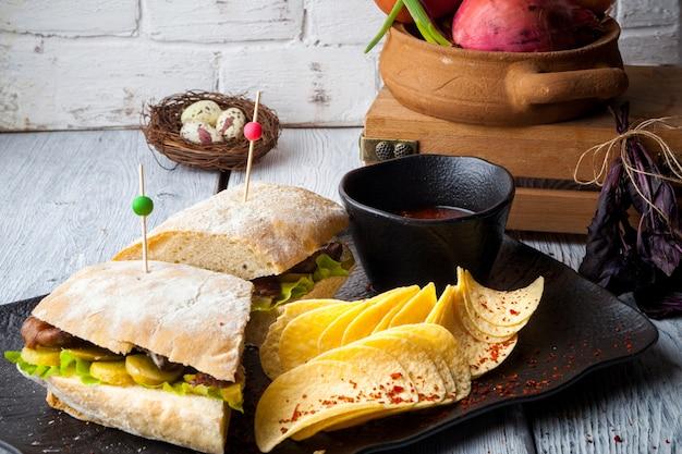 Seitenansicht club sandwich und kartoffel cheeps in teller mit sauce