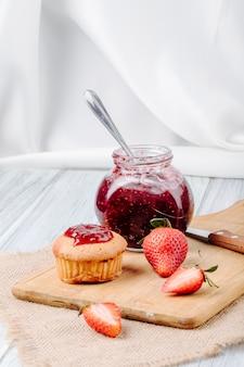 Seitenansicht cupcake mit erdbeermarmelade frisches erdbeermesser und brett auf weißem hintergrund