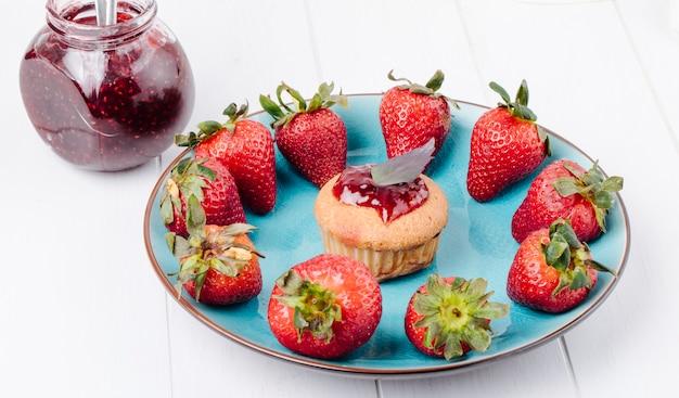 Seitenansicht cupcake mit erdbeermarmeladenbasilikum und frischer erdbeere auf einem teller