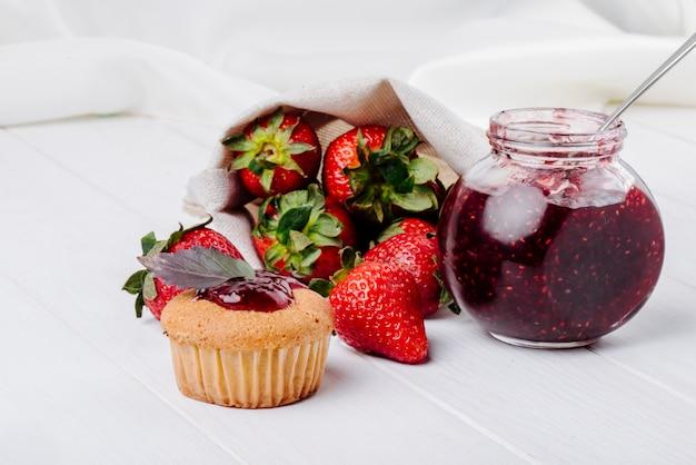 Seitenansicht cupcake mit erdbeermarmeladenbasilikum und frischer erdbeermarmelade auf weißem hintergrund
