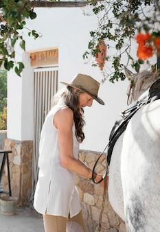 Seitenansicht der älteren bäuerin, die einen sattel auf ihrem pferd auf der ranch setzt