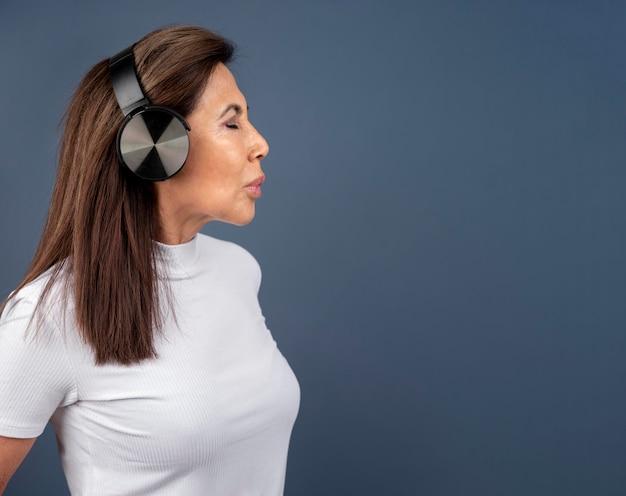 Seitenansicht der älteren frau, die musik über kopfhörer hört