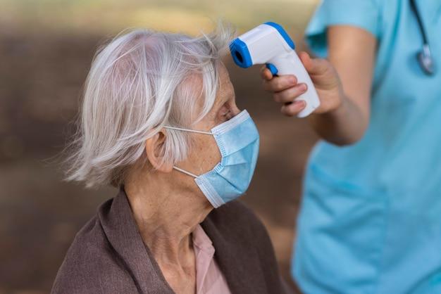 Seitenansicht der älteren frau mit der medizinischen maske, die ihre temperatur überprüft