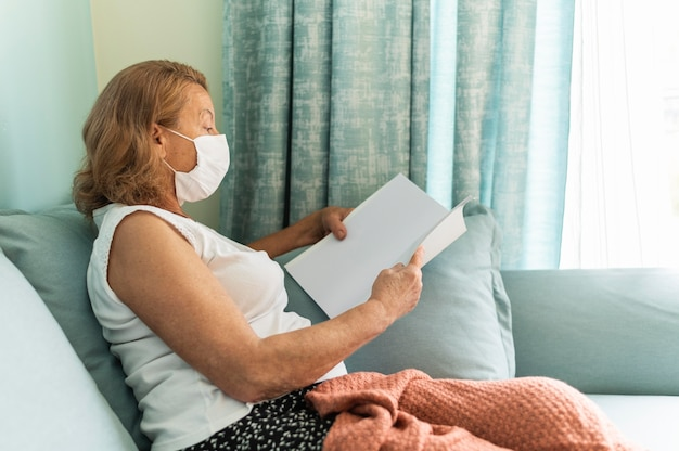 Seitenansicht der älteren frau mit der medizinischen maske zu hause während der pandemie, die ein buch liest