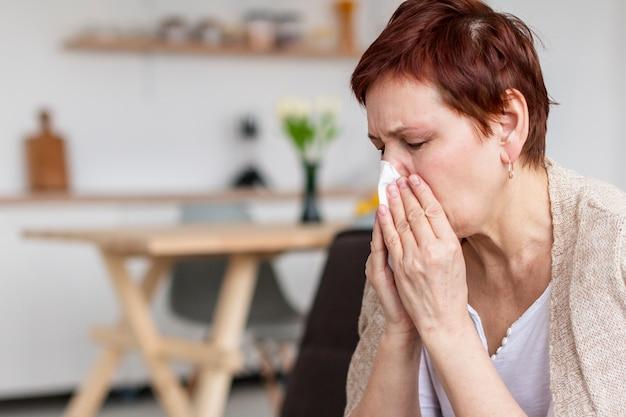Seitenansicht der älteren frau mit grippe