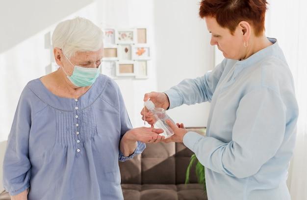 Seitenansicht der älteren frauen zu hause unter verwendung des händedesinfektionsmittels
