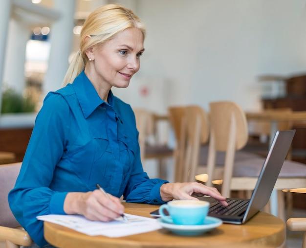 Seitenansicht der älteren geschäftsfrau des smileys, die am laptop mit papieren arbeitet