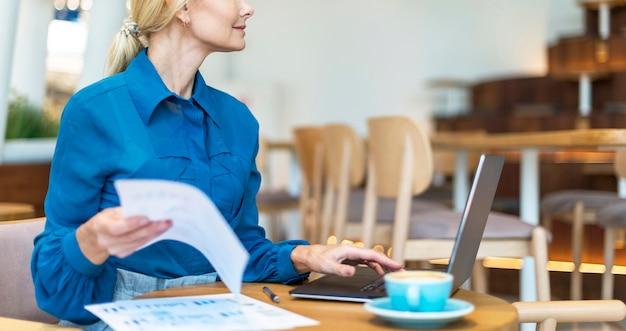Seitenansicht der älteren geschäftsfrau, die am laptop arbeitet, während tasse kaffee hat