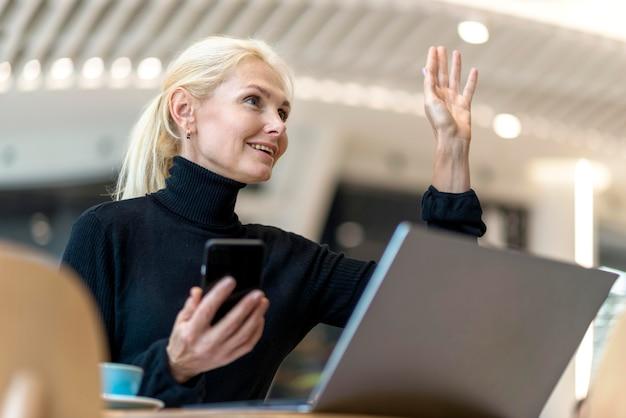 Seitenansicht der älteren geschäftsfrau, die etwas bestellt, während sie am laptop arbeitet