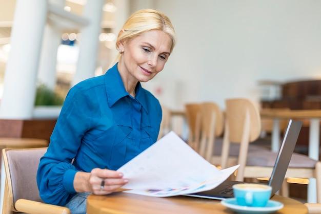 Seitenansicht der älteren geschäftsfrau, die mit papieren handelt