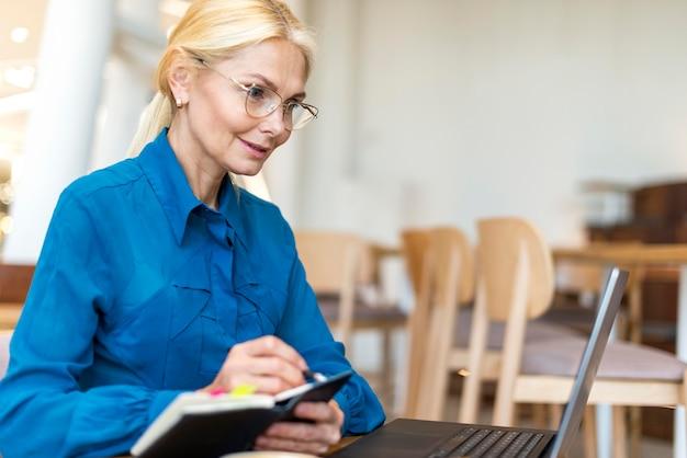 Seitenansicht der älteren geschäftsfrau mit brille, die am laptop arbeitet