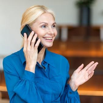 Seitenansicht der älteren smiley-frau, die am telefon während der arbeit spricht