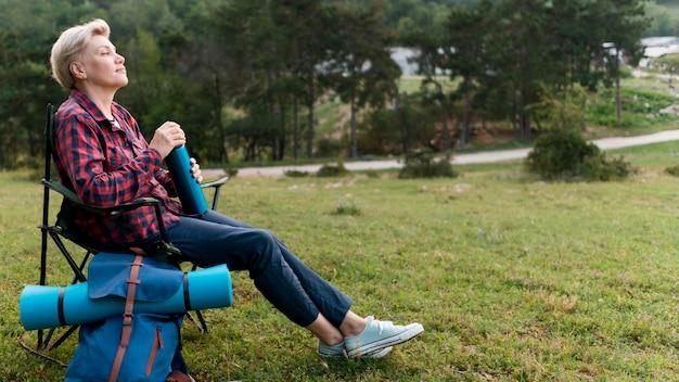 Seitenansicht der älteren touristenfrau, die eine pause im freien macht