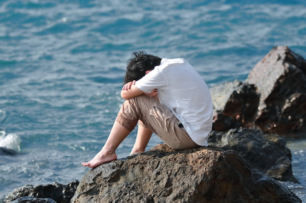 Seitenansicht der angst betonte asiatische mannumarmung sein knie und sitzen am seeufer.