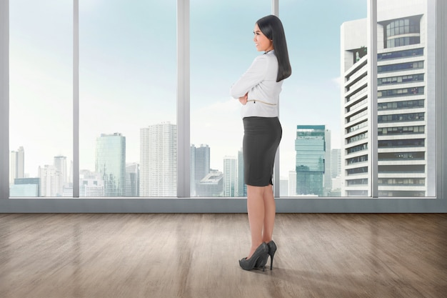 Seitenansicht der asiatischen geschäftsfrau, die auf büroraum steht