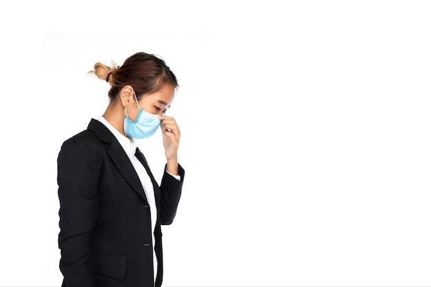 Seitenansicht der asiatischen geschäftsfrau, die chirurgische gesichtsmaske in der formalen schwarzen anzugjacke trägt, berühren ihre nase, studiobeleuchtung lokalisiert auf weißem hintergrund, coronavirus, covid-19-konzept