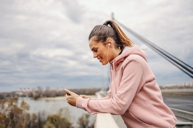 Seitenansicht der attraktiven lächelnden positiven jungen sportlerin, die sich auf brückengeländer stützt und smartphone für das lesen der nachricht und das hören von musik verwendet. konzept des städtischen lebens.