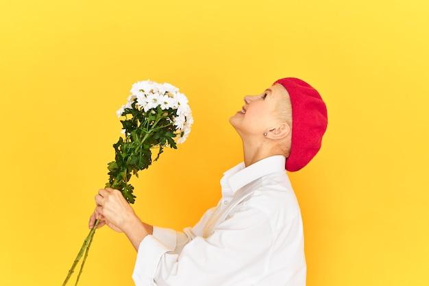 Seitenansicht der aufgeregten überglücklichen älteren frau in der stilvollen baskenmütze und im freizeithemd, die gegen leeren gelben studiowandhintergrund aufhalten, der blumen hält und nach oben schaut, als würde er blumenstrauß werfen
