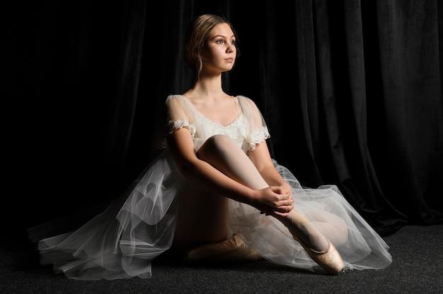 Seitenansicht der ballerina aufwerfend im ballettröckchenkleid und in den pointe schuhen