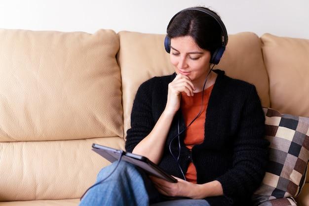 Seitenansicht der besorgten frau mit kopfhörern, die einen kranken freund mit elektronischem gerät anrufen. soziales distanzkonzept in quarantäneisolation zu hause.
