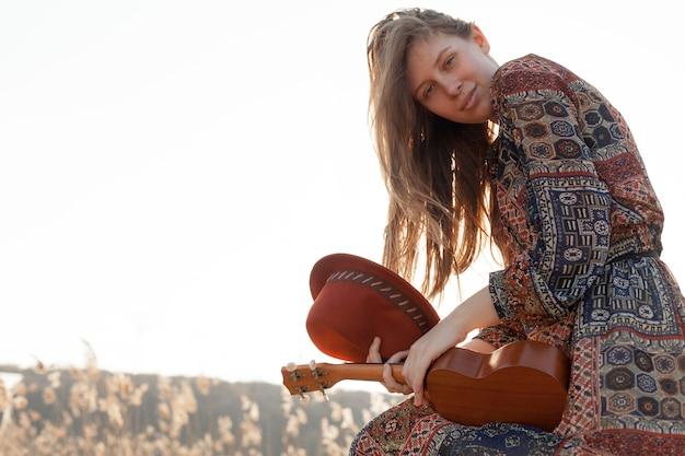 Seitenansicht der böhmischen frau, die mit hut und ukulele in der natur aufwirft