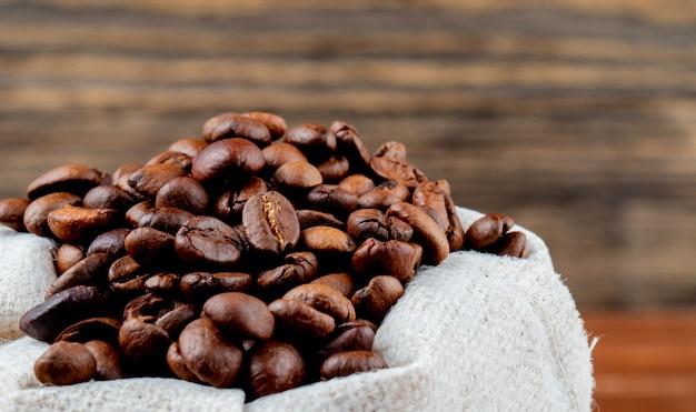 Seitenansicht der braunen kaffeebohnen in einem sack auf rustikalem tisch