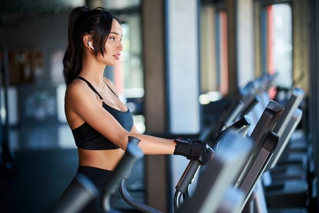 Seitenansicht der brünetten frau in der schwarzen sportbekleidung und in den kabellosen kopfhörern, die hartes cardio-training auf orbitrek tun.