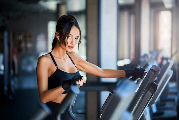 Seitenansicht der brünetten frau in sportbekleidung und kabellosen kopfhörern, die cardio-training auf orbitrek tun