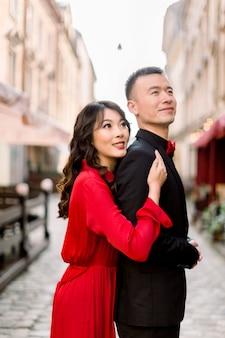 Seitenansicht der chinesischen frau im roten kleid, die hand auf schulter ihres mannes im schwarzen anzug hält