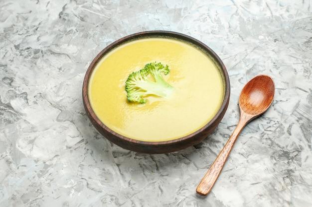 Seitenansicht der cremigen brokkolisuppe in einer braunen schüssel und im löffel auf grauem tisch