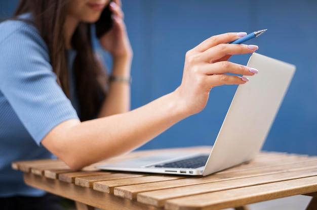 Seitenansicht der defokussierten frau, die am laptop arbeitet, während auf smartphone spricht