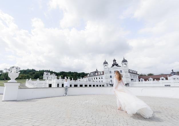Seitenansicht der eleganten braut geht zu ihrem bräutigam auf einem hintergrund von weißen gebäuden