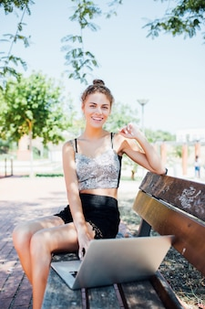 Seitenansicht der erfreuten brünetten frau, die auf bank im park sitzt und laptop-computer verwendet