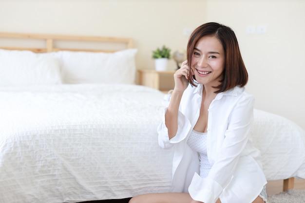 Seitenansicht der erwachsenen freiberuflich tätigen asiatischen frau im weißen hemd, das an computer und handy im schlafzimmer mit glücklichem lächelndem gesicht arbeitet