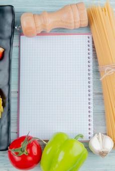 Seitenansicht der fadennudel-pfeffer-knoblauch-tomate und des notizblocks auf holztisch mit kopienraum