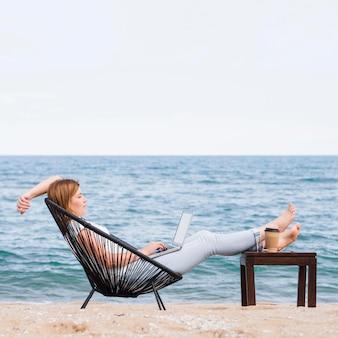 Seitenansicht der frau am strand, die am laptop arbeitet