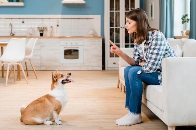 Seitenansicht der frau auf der couch, die ihren hund trainiert