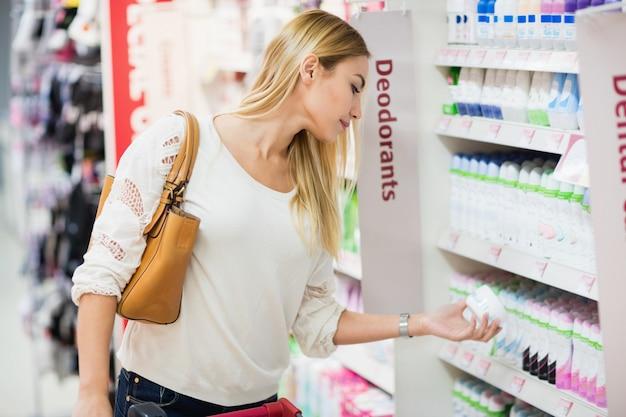 Seitenansicht der frau desodorierendes mittel wählend