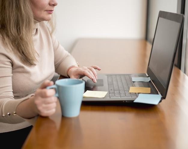 Seitenansicht der frau, die am laptop im büro arbeitet
