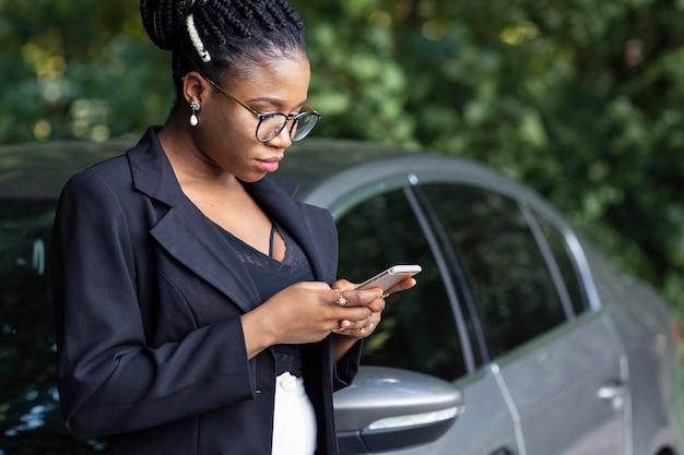 Seitenansicht der frau, die auf ihrem auto beim betrachten des smartphones ruht