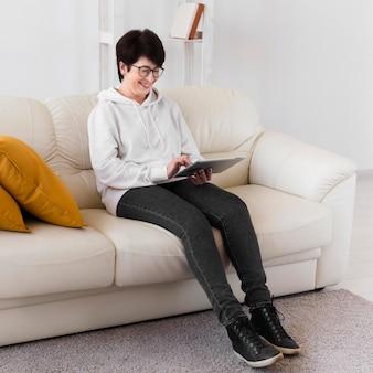 Seitenansicht der frau, die auf sofa mit tablette sitzt