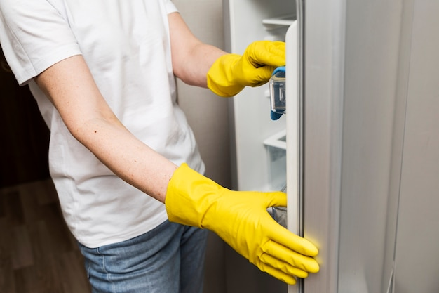 Seitenansicht der frau, die den kühlschrank reinigt