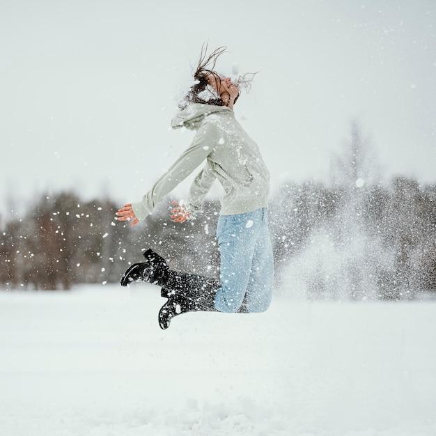 Seitenansicht der frau, die draußen im winterschnee springt