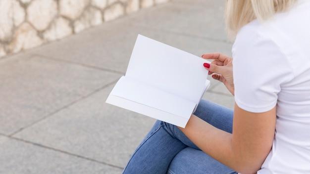 Seitenansicht der frau, die draußen sitzt und buch mit kopienraum liest