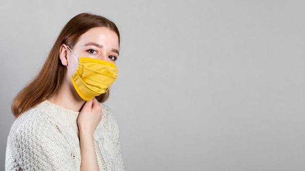 Seitenansicht der frau, die eine medizinische maske mit kopienraum trägt