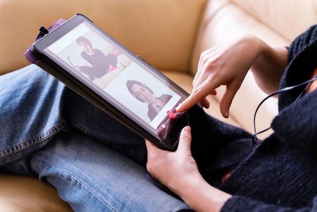 Seitenansicht der frau, die einen freund mit technologiegerät für video-chat und gespräch anruft. bleiben sie zu hause und soziale distanz konzept.