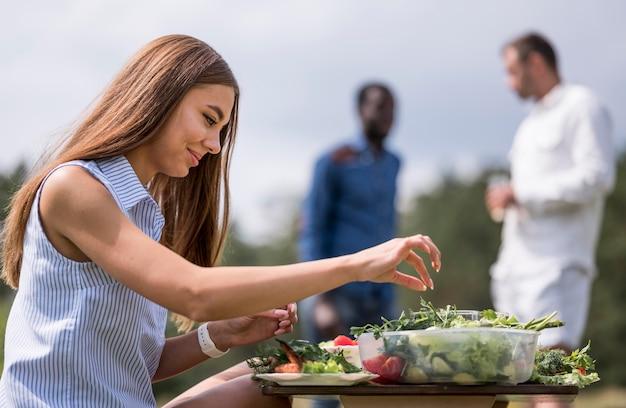 Seitenansicht der frau, die essen für grill vorbereitet